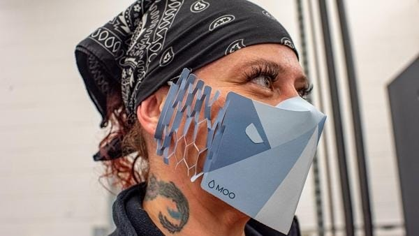 Press operator Samantha Slater wears one of the custom masks while working a shift. The Lincoln company Moo believes it's the first in the world to make recyclable one-use paper face masks with logos printed on them.