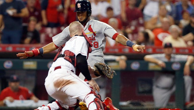 St. Louis Cardinals first baseman Jose Martinez (58) scores against Cincinnati Reds catcher Tucker Barnhart (16) during the seventh inning at Great American Ball Park.