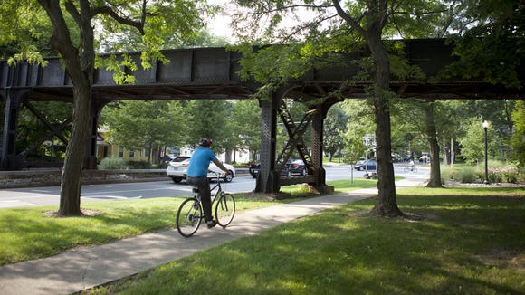 A bicyclist rides under the CSX bridge on North Main Street in Pittsford.