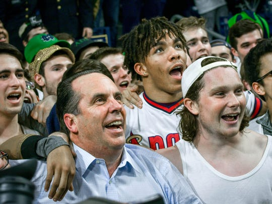Coach Mike Brey sings the Notre Dame alma mater with the student section after his team defeated the Florida State Seminoles 84-72 on Feb. 11.