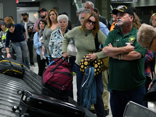 Travelers waiting for and collecting their luggage at McGhee Tyson Airport Friday, Nov. 17, 2017.