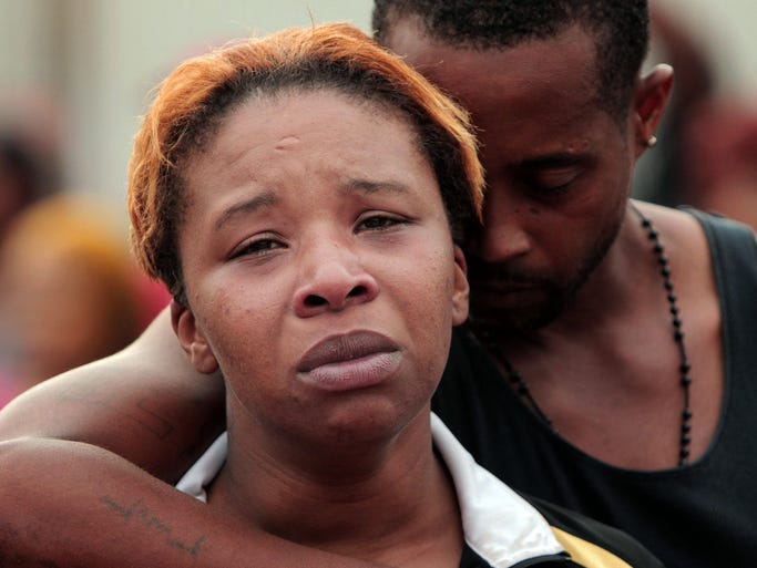 Lesley McSpadden, left, is comforted by her husband, Louis Head, after her 18-year-old son, Michael Brown was shot by police and killed in the middle of the street in Ferguson, Mo., A spokesman with the St. Louis County Police Department, which is investigating the shooting at the request of the local department, confirmed a Ferguson police officer shot the man. The spokesman didn't give the reason for the shooting.