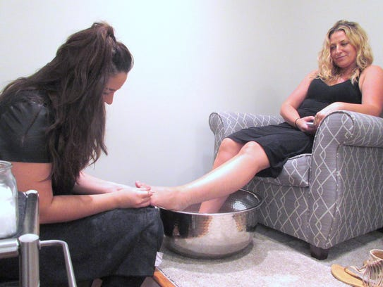 Namasté employee Emily Ward gives a pedicure to Brianne
