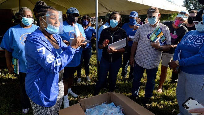 Jamilia Gates, left, of the Erie Chapter of Zeta Phi Beta Sorority Inc., passes out masks to volunteers gathered Saturday at 22nd and Wallace streets in Erie. The outreach event was organized by United Clergy of Erie to inform residents about COVID-19.