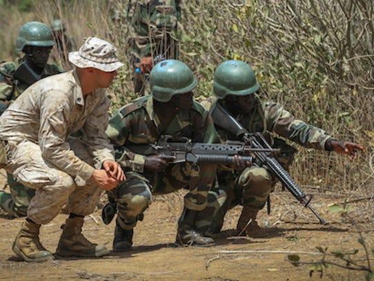 US Marine Sgt. Bryan Ballard observes Senegalese soldiers
