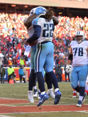 Titans running back Derrick Henry (22) is congratulated by offensive tackle Dennis Kelly (71) after scoring during the second half Sunday.