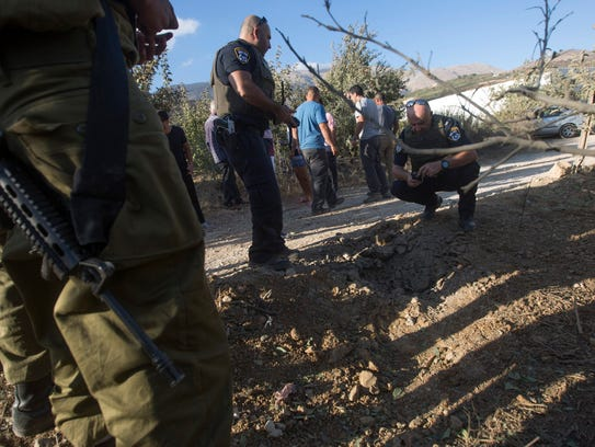 Israeli police and local Druze citizens inspect a plantation
