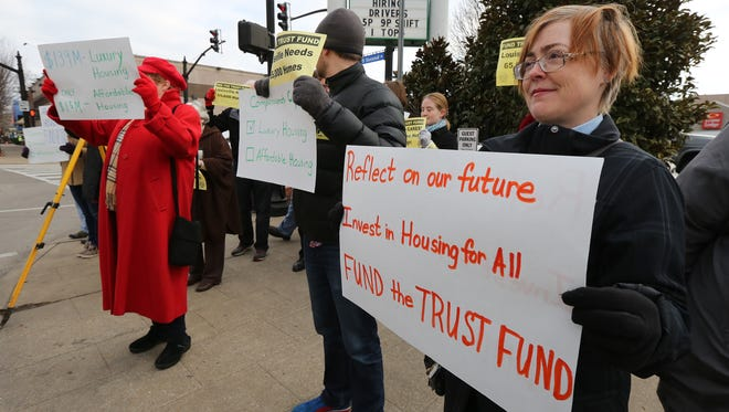 Dawn Cooley, minister with First Unitarian Church, stands with the group CLOUT (Citizens of Louisville Organized and United Together), protest across the street from the groundbreaking.  They contend that the city should be funding the Affordable Housing Trust Fund rather than give incentives to the Omni.