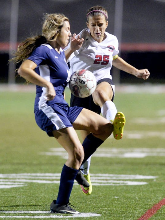 Dallastown's Natalie Gettle, left, blocks a pass by Dover's Brooke Firestone during the second overtime period in Thursday's YAIAA girls' soccer tournament championship game. Dallastown defeated Dover, 3-2, in double overtime.
