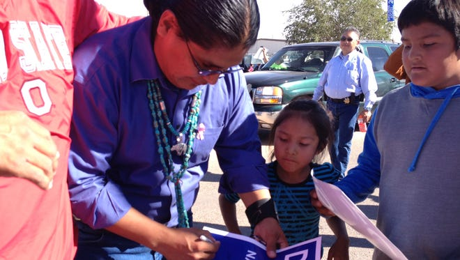 Navajo presidential candidate Chris Deschene autographs election placards at the Western Navajo Nation Fair on Oct. 18, 2014, in Tuba City.