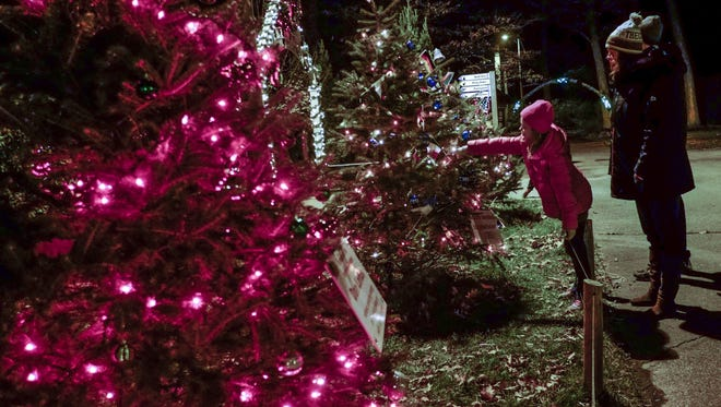 Alivia Burghdoff, 9, points out the different flag decorations to her mom Missy on a tree at Potter Park Zoo's annual Wonderland of Lights Nov. 27, 2016.