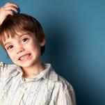 Studio shot of smiling boy scratching head