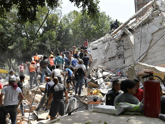 People remove debris of a collapsed building looking