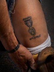 Mills shows his tattoo of the Purple Heart medal on his calf. Mills nearly lost his life during his tour of duty in Iraq in 2005.