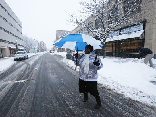 Alesha Jones crosses Main Street in the City of Poughkeepsie