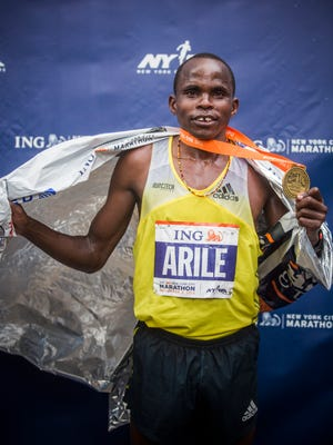 A Kenyan marathoner shows off his hardware after finishing among the top runners at the New York City Marathon.