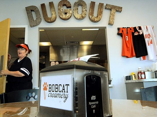 Bobcat Creamery cook Connie Feeser exits the kitchen to greet a customer Wednesday. Below, employees Jo Jennings, left, and Dorothy Hogan handle the lunch rush. The sports-themed restaurant, which opened last week, has a board of directors made up of Northeastern High School students.