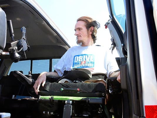 Chris Sauerbaum, 33, of York City, demonstrates the door lift on his custom GMC pickup truck Thursday at Cousler Park. Sauerbaum, who has chronic inflammatory polyneuropathy, had the truck outfitted so he can operate it with hand controls instead of pedals. Watch the video at yorkdispatch.com.