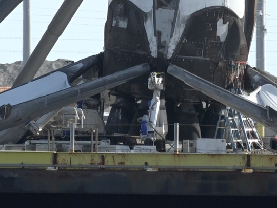 """A closeup shot of SpaceX's drone ship """"robot,"""" which is a flat piece of equipment with white cylinders that attach to the Falcon 9 first stage."""
