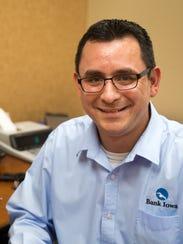Mario Flores, a mortgage lender at Bank Iowa, sits