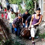 A group of men help to remove bodies of people executed in the capital city of Tegucigalpa, Honduras, on Nov. 25, 2015. Honduras once had the highest murder rate in the world, but El Salvador may have overtaken its Central American neighbor in 2015.
