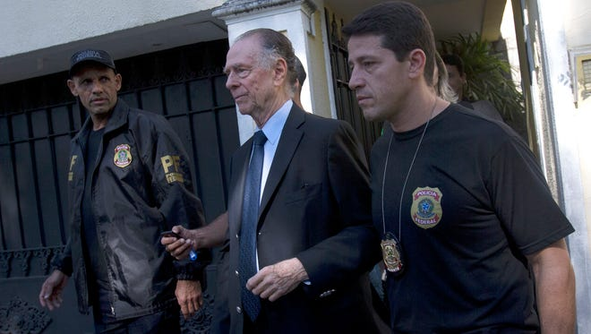 Carlos Nuzman, President of the Brazilian Olympic Committee, center, is escorted by federal police officers after being taken into custody at his home, in Rio de Janeiro, Brazil.