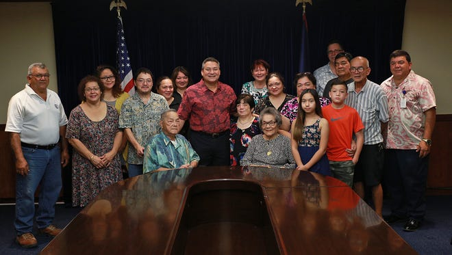 Gregorio Tenorio, seated left, and Lucia McDonald, seated right, shown with family and officials, are the 2016 Liberation Day Parade grand marshals.