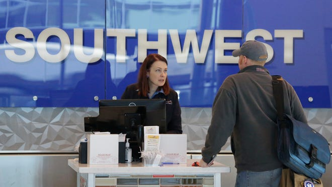 A Southwest Airlines agent helps a traveler at Love Field airport in Dallas the day before Thanksgiving. Southwest is hiring more flight attendants.