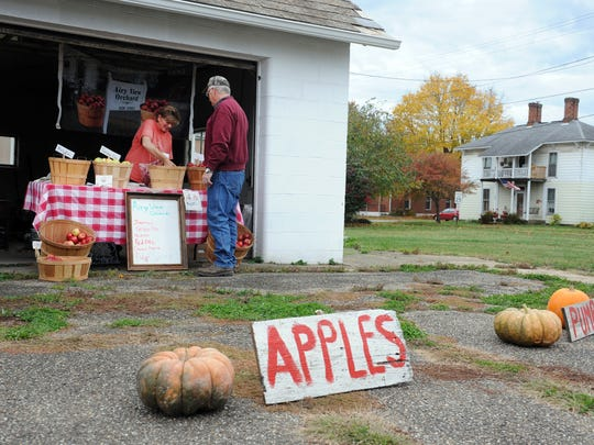 Holly Crown, 53, of Airy View Orchard in Dresden, sells apples to Bob Miller, 59, of Frazeysburg, at her aunt and uncle's property at the corner of State and Raiders roads in Frazeysburg. Crown took over the orchard from her late grandfather, John Francis Shaw, and is a member of the fourth generation to run the farm.
