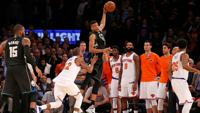 Giannis Antetokounmpo gets the ball in the waning seconds as the Knicks' Lance Thomas defends.