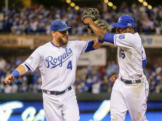 Kansas City Royals center fielder Lorenzo Cain (6) and left fielder Alex Gordon (4) celebrate after Cain made a leaping catch for a ball hit by Los Angeles Angels' Howie Kendrick during the fifth inning of Game 3 of baseball's AL Division Series in Kansas City, Mo., Sunday, Oct. 5, 2014. (AP Photo/Charlie Riedel)
