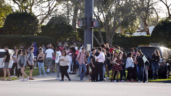 Students wait outside the Marjory Stoneman Douglas