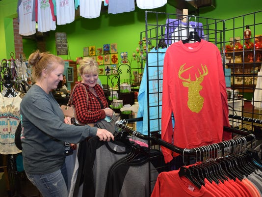 """Shelby Hilton (left) and mother Lisa Brasher look at shirts at Funky Fleur de Lis as they shopped on Small Business Saturday. Hilton lives in Texas, her mother said, and likes to shop at Funky Fleur de Lis when she comes back home. """"This is one of her favo"""