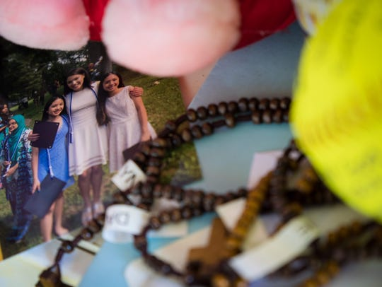 A photo of Danna and twin sisters Melissa and Allison is surrounded by messages of condolences on the front porch of the Trinidad family home in Teaneck, N.J.