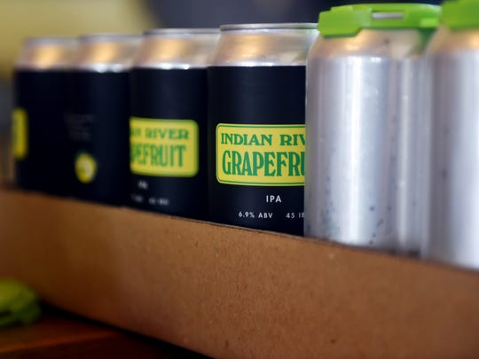 Labels for Orchid Island Brewery's Indian River Grapefruit, an American IPA, are placed on cans to be filled and sold. Orchid Island Brewery sources locally grown citrus for all of their beers.