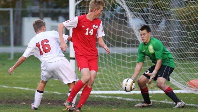 Canton's Carter Schenk (center) directs the ball Friday toward Livonia Churchill goalkeeper Nathan Guzowski. At left for the Chargers is Kyle Benedict.