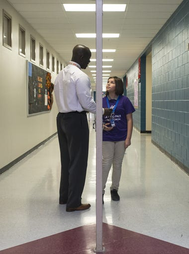 Principal Eric Atuahene (left) talks with Aliyah Rosas (Junior Coach, 4th grade), Nov. 7, 2017, in the hall at Quentin Elementary School, 11050 W. Whyman Ave., Avondale.