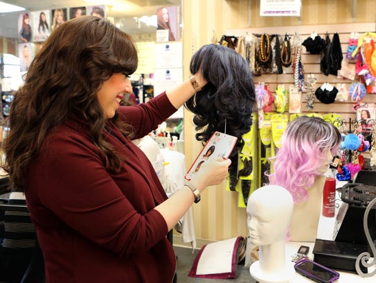 Rivkie Feiner of Monsey checks out Purim wigs at L'Image
