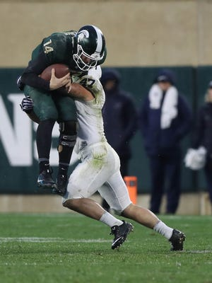 Michigan State quarterback Brian Lewerke, here tackled and carried by Penn State's Brandon Smith, earned a ton of respect around the Big Ten last season.