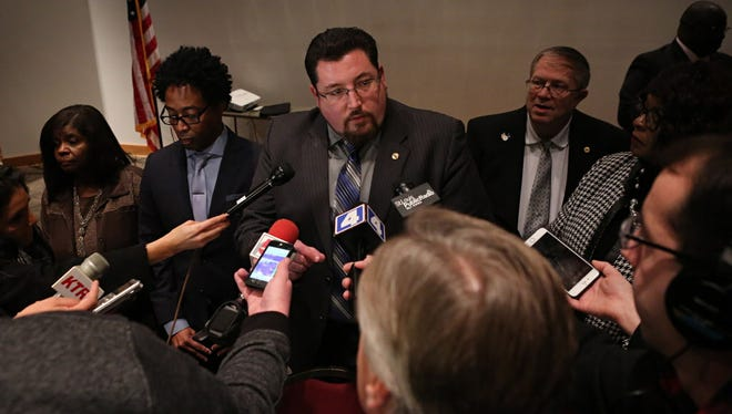 Ferguson mayor Mayor James Knowles III, center, talks to the media after the Ferguson, Mo., city council meeting in Ferguson on Tuesday, Feb. 9, 2016, where the council voted to approve a modified consent decree with the United States Department of Justice.