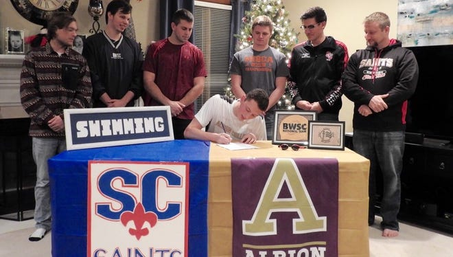With the Blue Water Swimming looking on, St. Clair's Evan Wonner signs to Albion College swimming.