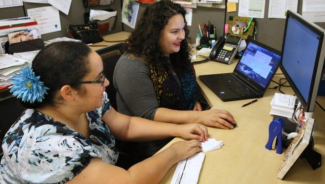 Caroline Gómez-Tom (right), a navigator program manager for the Milwaukee Enrollment Network, helps Joelisa Castillo of Milwaukee update her coverage Tuesday at Community Advocates.