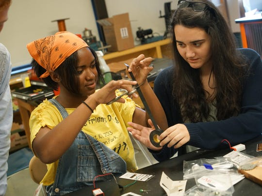 Sophomore Tommi Le Williams (center), 15, and junior Anna Conway, 17, put together electrical circuits in their Newark High School Engineering II class that meets in the maker space created for design projects.