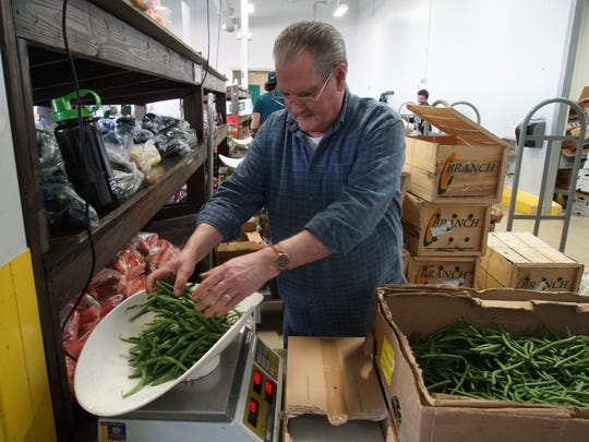 Al Brown weighs fresh green beans before bagging them up for sale at Produce Junction.