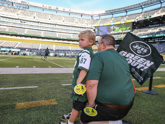 Neal Spickert-Fulton, a 5-year-old Morris Plains cancer patient visits N.Y. Jets/Falcon game at MetLife Stadium as SNYÕs Dream Day winner on August 21, 2015. Neal takes it all in while leaning on his father, Shawn Spickert-Fulton.
