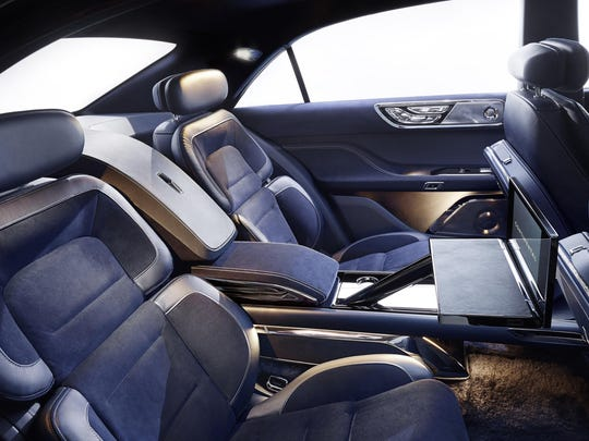 Suede rear seats with footrests extend into space created by pushing the front passenger seat up to the dashboard. Briefcases are integrated into the seat backs for storage. The champagne cup holders remain intact.