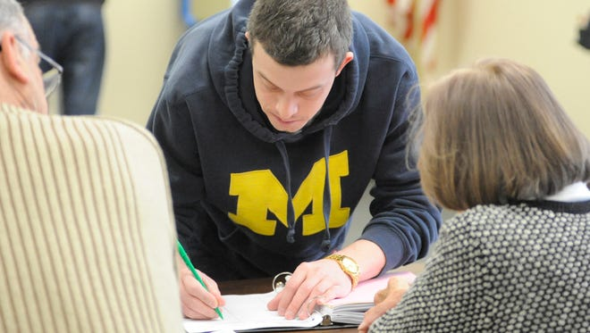 Manitowoc resident Benjamen Weber signs in to vote Tuesday at the city's District 9 polling station for the spring election.