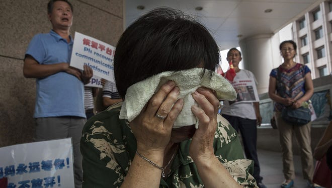 Bao Lanfang, a Chinese relative of missing passengers on Malaysia Airlines flight MH 370 cries as she waits for information outside the airline's office on August 6, 2015 in Beijing, China.