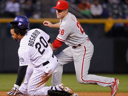 Philadelphia Phillies second baseman Chase Utley (26) tags out Colorado Rockies' Wilin Rosario at second during the fourth inning of a baseball game Wednesday, May 20, 2015, in Denver.  (AP Photo/Jack Dempsey)