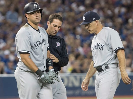 New York Yankees manager Joe Girardi comes out to check on Gary Sanchez after he was hit by a pitch in the eighth inning of their baseball game against the Toronto Blue Jays in Toronto on Tuesday, Aug. 8, 2017. (Fred Thornhill/The Canadian Press via AP)